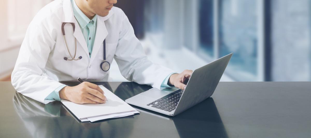 Médecin de sexe masculin assis devant un ordinateur portable