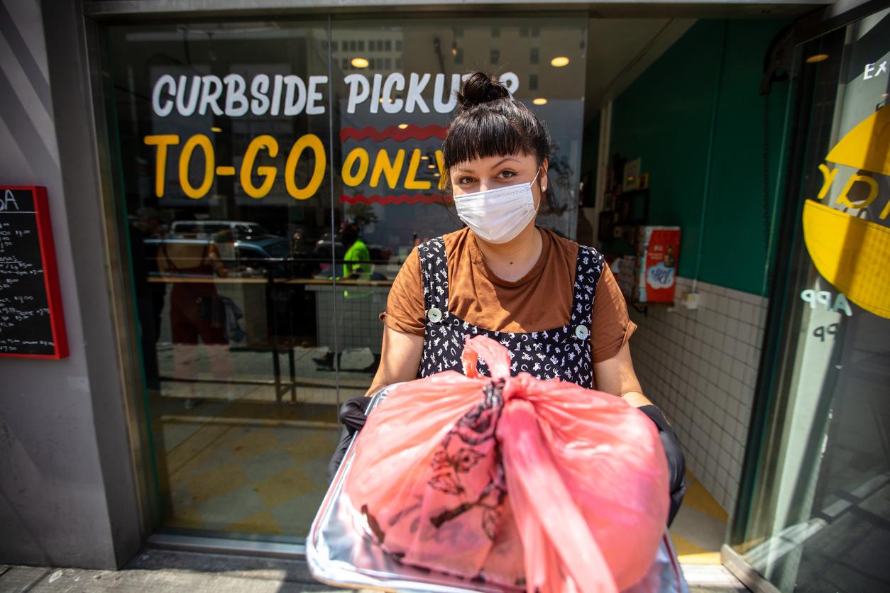 une jeune femme hispanique remet un ordre de bordure de rue