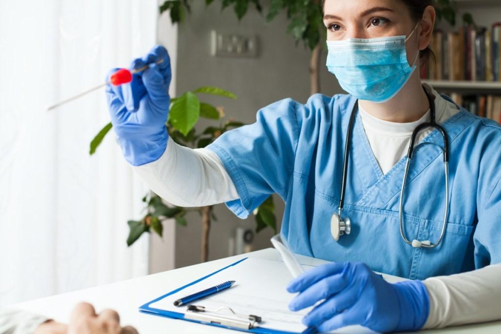 jeune femme médecin blanche donnant un test d'écouvillonnage de coronavirus