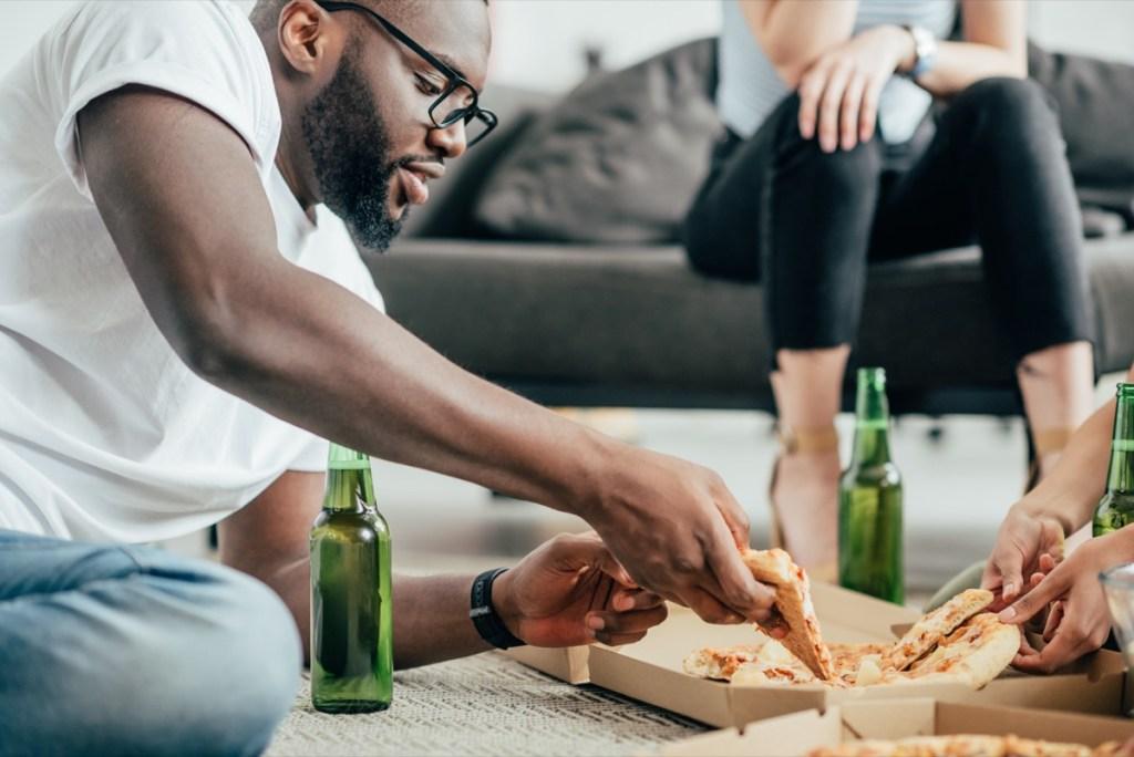 homme mangeant de la pizza et buvant de la bière sur le plancher, sexe sain après 40