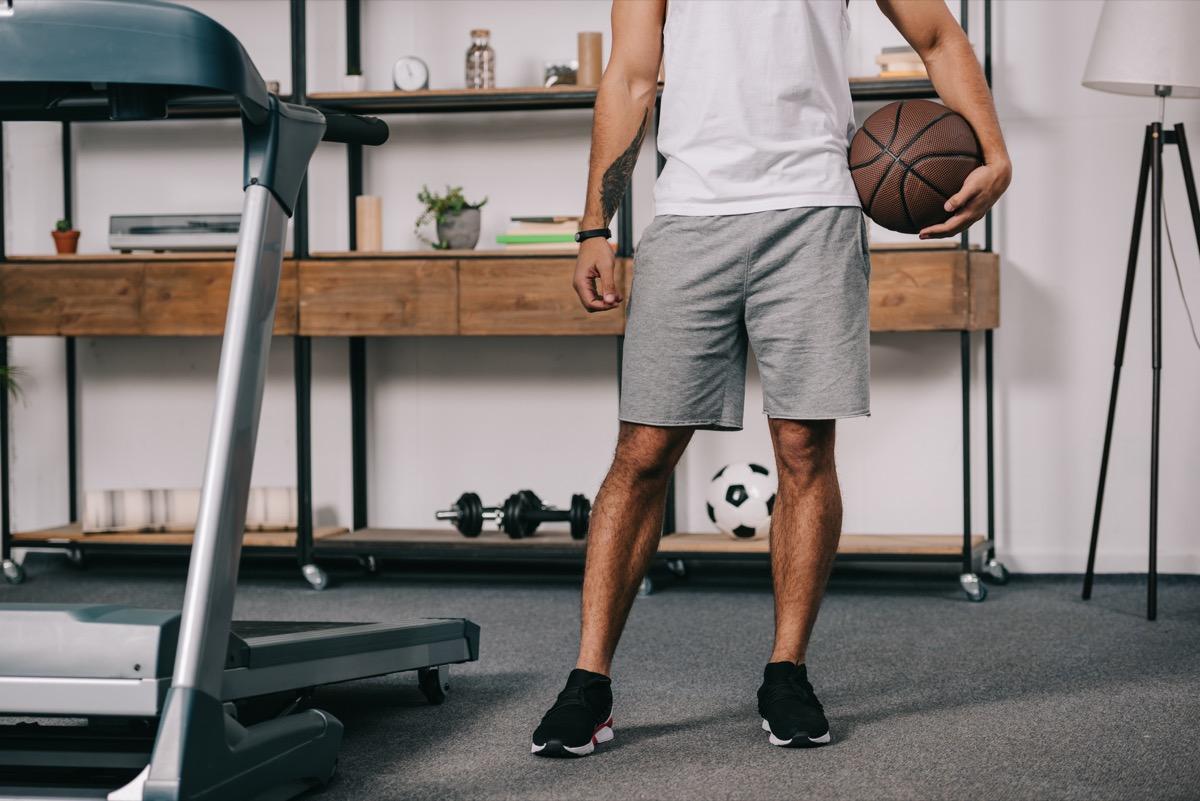 homme tenant un ballon de basket debout à côté d'un tapis roulant