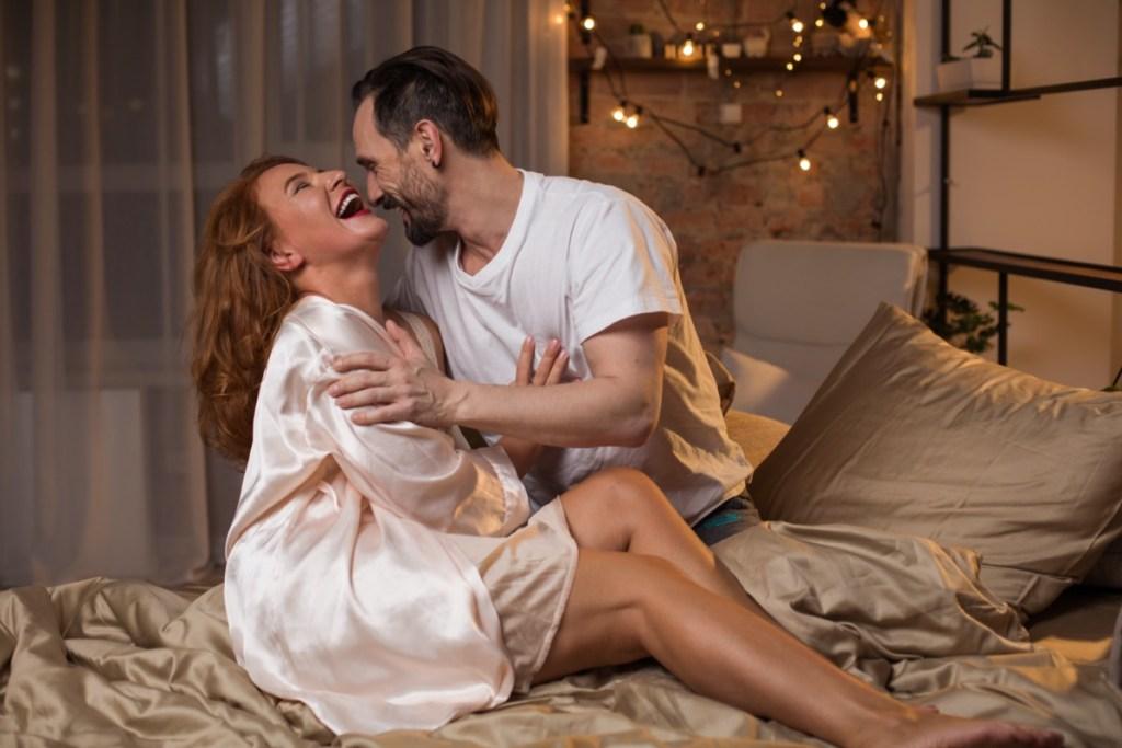 femme mature blanche en robe rose clair et homme mature blanc en t-shirt blanc riant et se serrant dans son lit
