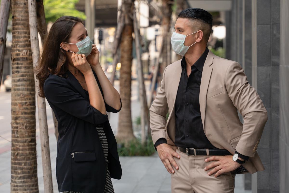 homme et femme parlant tout en portant des masques