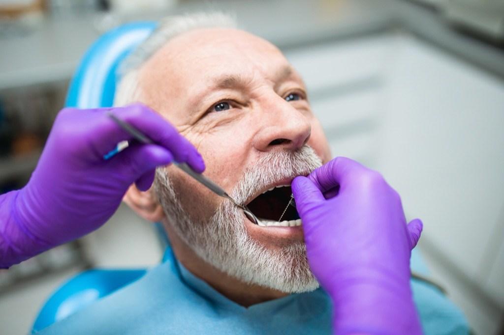 Un homme plus âgé chez le dentiste vérifie ses gencives, des questions de santé après 40