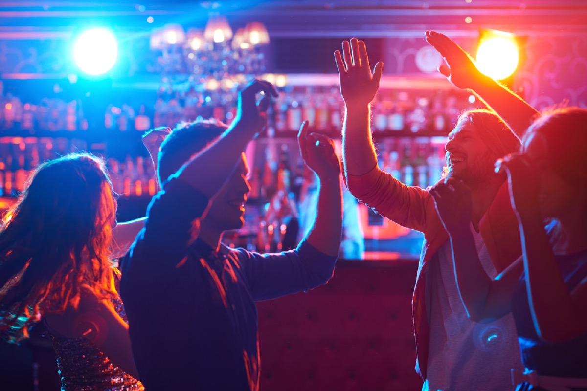 jeunes dansant dans un bar avec des lumières rouges et bleues