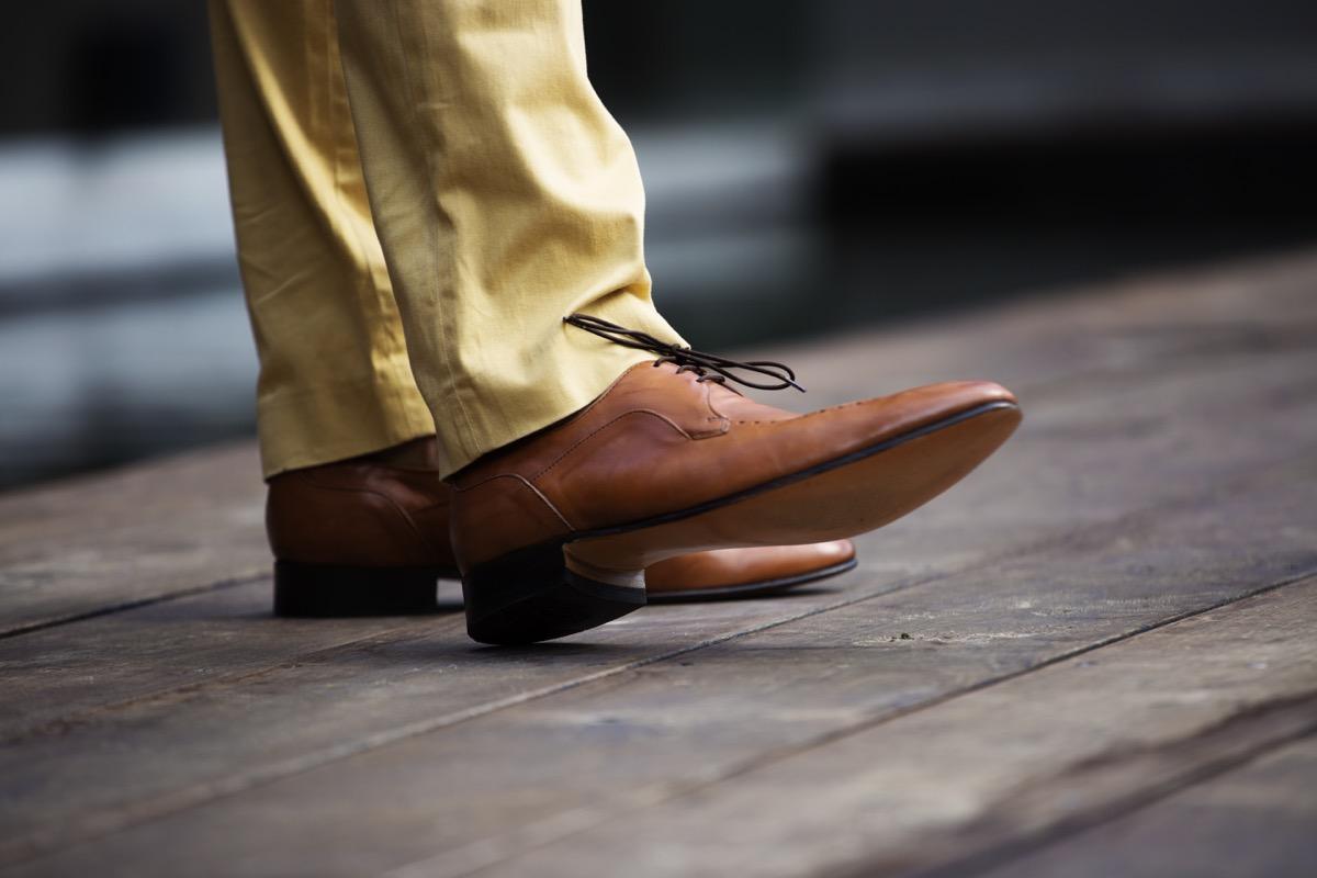 Jambes du Mans dans des chaussures en cuir marron tirées sous le genou