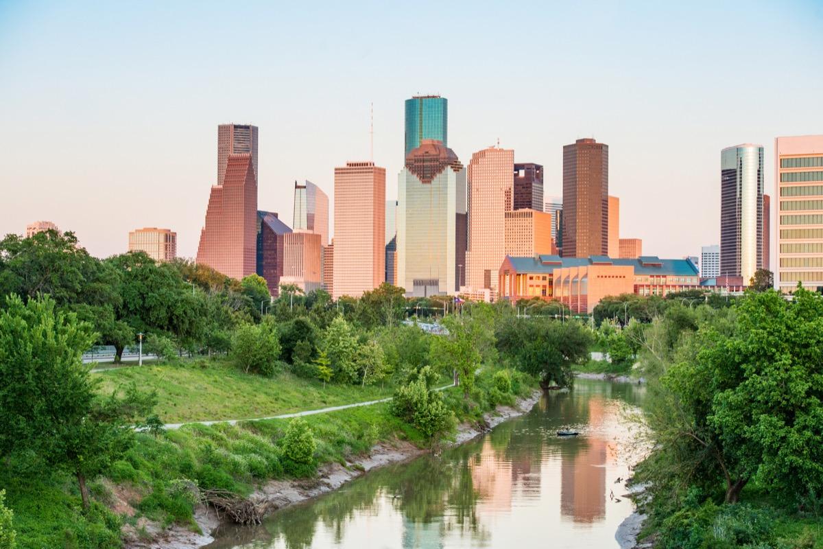Ceci est une photographie du parc Buffalo Bayou avec un ruisseau menant vers les bâtiments du centre-ville de Houston, au Texas au printemps.