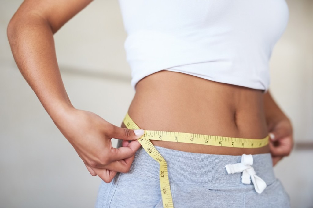 Femme mesurant sa taille pour prendre du poids
