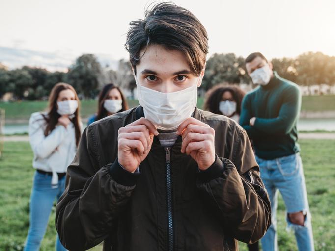 Un jeune homme de race blanche portant un masque avec un groupe de ses amis debout derrière lui